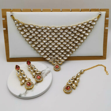 Vaani Peach/Pink Statement Choker Earring and Tikka Set fill set with necklace on stand
