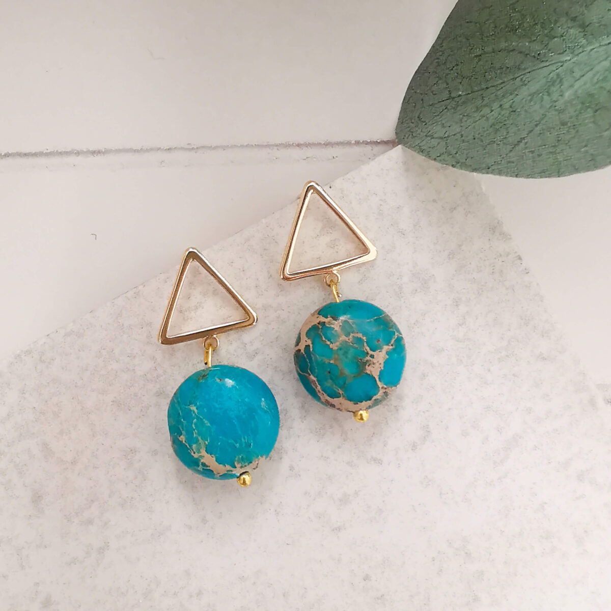 REVA - 18K Gold Plated Unique Turquoise Stone Earrings against plain tile background