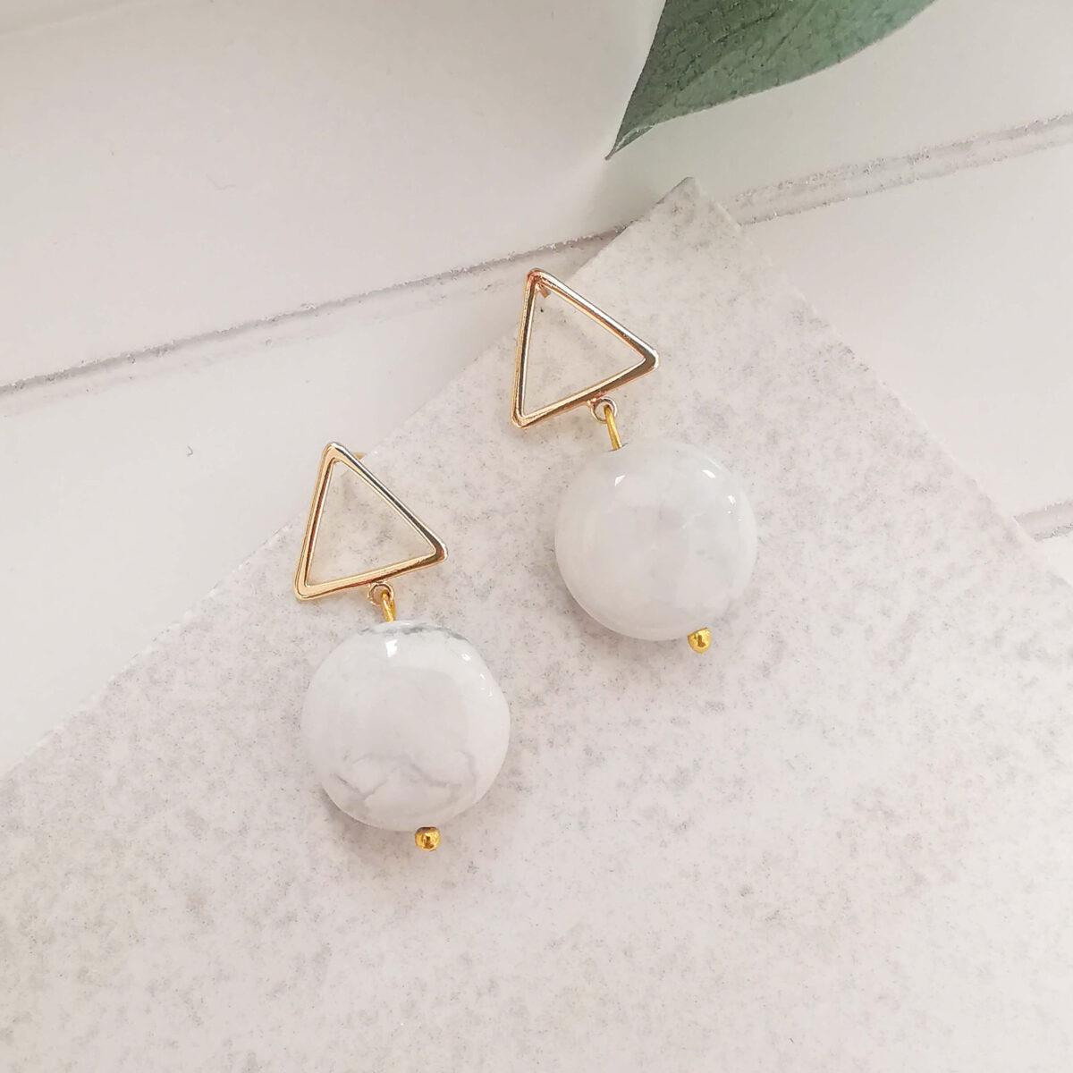 REVA - 18K Gold Plated White Marble Look Stone Earrings on a plain tile background