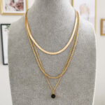AccentsUK Gold Snake Bone Necklace layered with Sarika Black Necklace and Gold Rope Necklace on grey mannequin