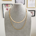 AccentsUK Gold Snake Bone Necklace layered with Gold Rope Twist Necklace on grey mannequin